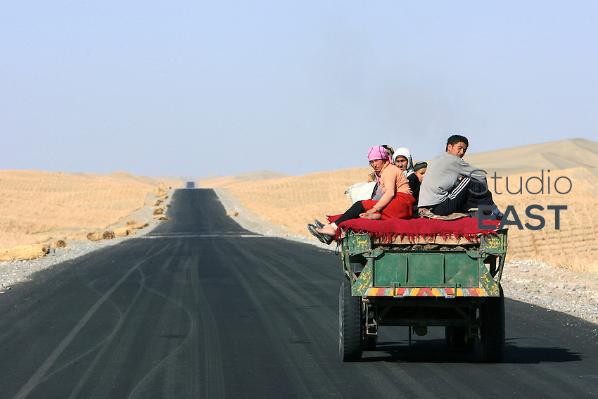 Uyghurs use a truck on the Desert highway to cross the Taklamakan desert in Xinjiang province, China, on October 12, 2006. The Taklamakan Desert is a desert in Central Asia, in the Xinjiang Uyghur Autonomous Region of China. Photo by Lucas Schifres/Pictobank