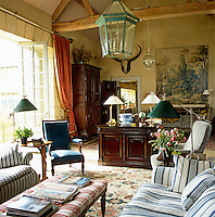 The drawing room is located in the former barn where one wall is dominated by an Aubusson tapestry cartoon above an antique Knole sofa and the centre of the room is furnished with comfortable sofas upholstered in cotton ticking