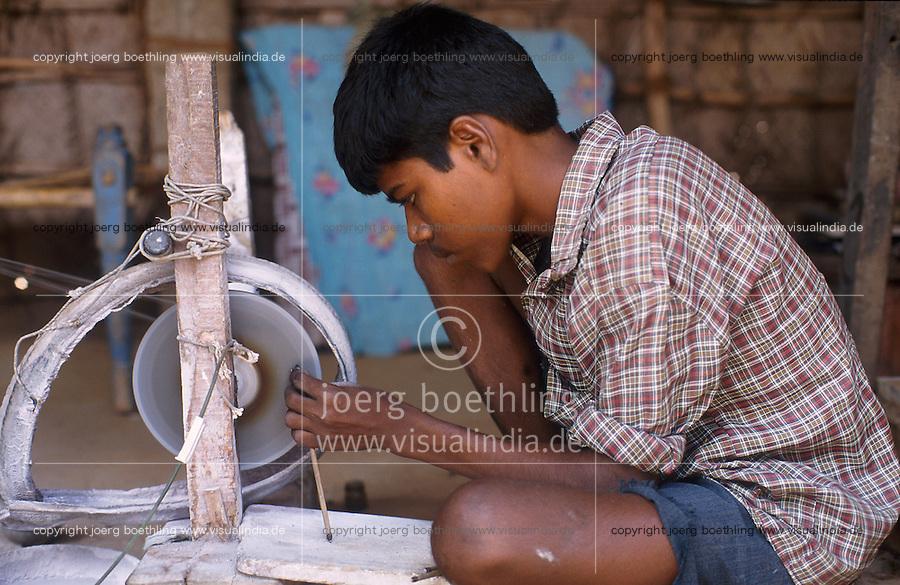 INDIA Tamil Nadu, Karur, child labour, boy work in a polishing unit for artificial synthetic gems, he is polishing the stones fixed with wax on bamboo sticks / INDIEN, Kinderarbeit, Junge arbeitet in einer kleinen Edelsteinschleiferei im Dorf V. Pudur bei Karur, hier werden Halbedelsteine und kuenstliche Edelsteine poliert
