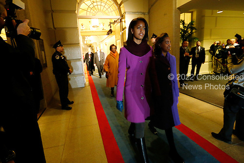 United States President Barack Obama's daughters Malia Obama (L) and Sasha Obama (R) are escorted through the corridor to the west door of the U.S. Capitol to begin swearing-in ceremonies in Washington, January 21, 2013. .Credit: Jonathan Ernst / Pool via CNP