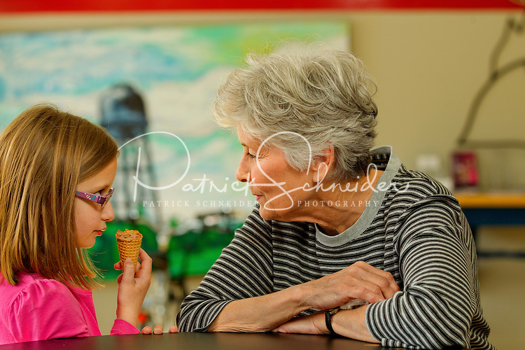 Lifestyle photography of Concord NC, where a grandmother and granddaughter relax and enjoy an icecream cone inside of the Cabarrus Creamery at 21 Union Street South in downtown Concord, North Carolina. One feature that makes the Cabarrus Creamery special is the local artwork for sale at the front of the store. Photo is part of a photographic series of images featuring Concord, NC, by Charlotte-based photographer Patrick Schneider.