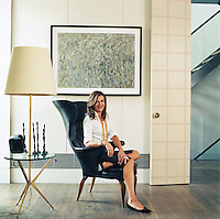 Portrait of Emma Roig sitting on a vintage chair designed by Fritz Henningsen in her living room
