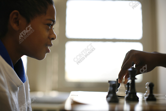 Boys playing chess at the Frederick Douglass Academy in Harlem, New York City, New York, July 25, 2007