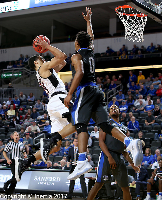 SIOUX FALLS, SD: MARCH 5: Zach Jackson #21 from Omaha hangs in the air looking for the shot against Mo Evans #0 from Fort Wayne during the Summit League Basketball Championship on March 5, 2017 at the Denny Sanford Premier Center in Sioux Falls, SD. (Photo by Dave Eggen/Inertia)