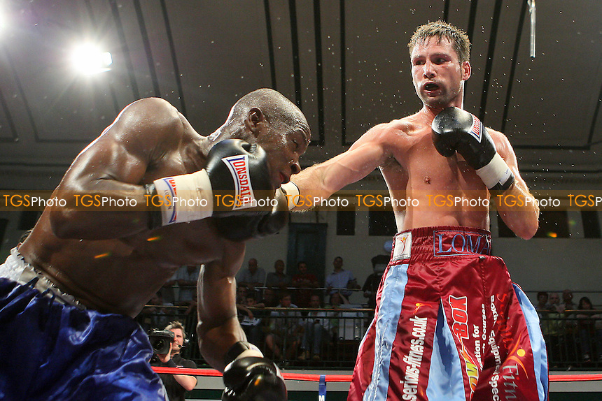 Michael Lomax (claret/blue shorts) defeats Stephen Okine in a Welterweight boxing contest at York Hall, Bethnal Green, promoted by Matchroom Sports / Barry Hearn - 09/07/10 - MANDATORY CREDIT: Gavin Ellis/TGSPHOTO - Self billing applies where appropriate - Tel: 0845 094 6026