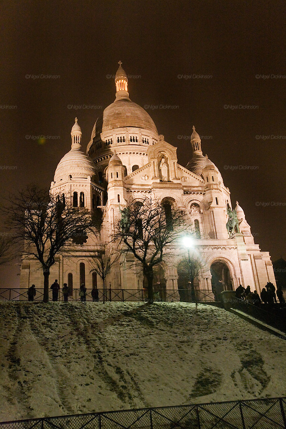CLIMATE CHANGE. Snow, Arctic temperatures and big freeze in Paris, France. The Basilica of Sacre-Coeur with tourists during a very cold and snowy night. Temperatures plummeted below zero, as low as -9. Very rarely, certainly not for decades, that Paris has experienced such freezing cold weather. Snow normally disappears in a couple of hours, this time it stuck around for days. Freak weather conditions and climate change can often be attributed to global warming and the ozone layer.