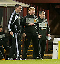 Motherwell Manager Stuart Mccall is held back by Fourth Official John McKendrick .