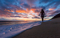 A woman takes in the sunset while walking along the beach at Yokohama Bay, West O'ahu.