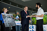 Ben Margolis, campaigns managers for TCK TCK TCK, presents an alarm clock to the Yvo de Boer, executive secretary of the UNFCCC, at the Barcelona Climate Talks. Members of 350.org hold photos of the actions that took place on Oct. 24 in the background.  (©Robert vanWaarden ALL RIGHTS RESERVED)
