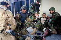 An Iraqi Minister of Interior Special Police Commando from  2nd Company, 2nd Battalion, 2nd Brigade receives medical first aid treatment   from a US ARMY medic after being shot in the leg by suspected insurgents while supporting the US Army 1st batt, 506th, 101st airborne div on a battalion size operation with the purpose of drawing insurgents to the open and destroying them from static observation posts and air support in  the Mul'Hab neighborhood of Eastern Ramadi, Al Anbar Province, Iraq on Sunday Feb 11 2006. 2nd Company came under fire during the operation returning several hundred  rounds back to the insurgents that were approaching them on civilian vehicles armed with machine guns. one hour in the operation an Iraqi senior non commissioned officer fired accidentally (  tech therm: negligent discharge) his AK 47 automatic rifle almost wounding several comrades and US military trainers that where operating next to him. the unit continued the mission making several tactical mistakes that opened the way for a suspected insurgent vehicle to approach from  close distance and fire accurately on the unit that was on an open street without cover. Two Commandos suffered injuries and were evacuated by the US Army Medivac system. A third received two rounds in his back armor plate but suffered no injuries. The operation lasted several more hours but after the accident the Commandos relaxed even further providing  very ineffective security.   The insurgency operates extensively in the Mul'Hab neighborhood attacking the coalition  and  Iraqi forces on a regular  bases.