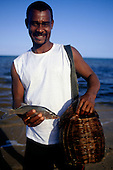 Bahia, Brazil. Smiling fisherman with his catch and his wicker basket to hold them.