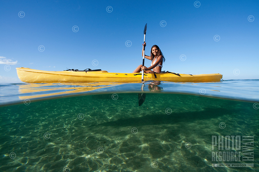 An above-and-below view of a woman kayaking in Lahaina, Maui.
