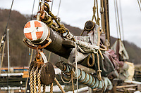 Close up photography of a wooden ship mast, with the ship waist and the sails secured to the masts.