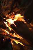 Ngoiwere Village, Mato Grosso State, Brazil. Kisedje (Suya),  warming feet by the fire.
