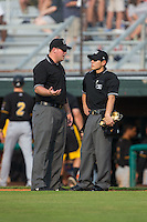 Umpire Ryan Barneycastle (left) chats with home plate umpire Kaz Endo between innings of the Appalachian League game between the Bristol Pirates and the Johnson City Cardinals at Howard Johnson Field at Cardinal Park on July 6, 2015 in Johnson City, Tennessee.  The Pirates defeated the Cardinals 2-0 in game one of a double-header. (Brian Westerholt/Four Seam Images)