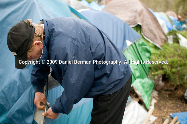 Tom Britz helps tie down his neighbor Bo Knox's tent after rainstorms destroyed the last one. Britz, who lives at the camp with his wife Linda, has been homeless since 2006.