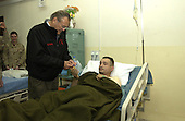 United States Secretary of Defense Donald H. Rumsfeld presents a Purple Heart to Sergeant Chris Scott 1st Brigade 25th Infantry Division while at Mosul Airfield, Iraq, December 24, 2004. Rumsfeld traveled to Iraq to show is support to service members and visit patients and staff from the 67th Combat Surgical Hospital. <br /> Mandatory Credit: James M. Bowman / DoD via CNP