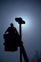 City worker installs new light bulbs in pole in school parking lot.