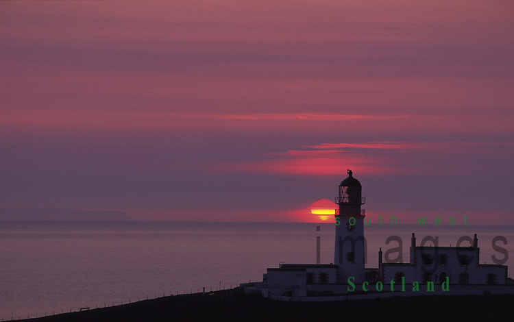 Sunset sun setting into sea North Channel behind Corsewall Lighthouse in the Rhins of Galloway Scotland UK