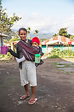 INDONESIA, Flores, a young woman with her baby stand front of their home in Waturaka Village