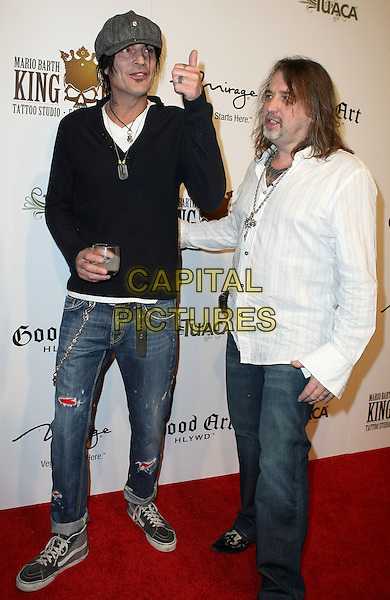 TOMMY LEE & MARIO BARTH .Mario Barth's King Ink Grand Opening at the Mirage Resort Hotel and Casino, Las Vegas, Nevada, USA, 10th April 2010.full length cap hat black drink hand tattoos top hoodie sweater jumper necklaces dog tag glass  smiling white shirt jeans hand thumb up gesture ripped trainers .CAP/ADM/MJT.© MJT/AdMedia/Capital Pictures.