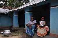 Monika Besra (42) and her husband Seiku Murmu posing with a Mother Teresa's photograph at their house at Danagram a village 40 kms away from Malda Town,  West Bengal, India. 20th August 2010.  Monica Besra says that her non curable tumour got cured on the first annivarsary of Mother Teresa's death by putting a Mother Teressa Medellion on the swollen part of her abdomen, which was recognized by the Vatican in the year 2002 and started the process of Mother Teresa's beatification, a major step towards sainthood.