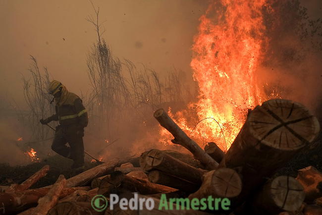 Flames and smoke rise into the air as a firefighters works at the site of a wildfire in Lousame, near A Coruna, on August 29, 2013. Spain is prone to forest fires in summer because of soaring temperatures, strong winds and dry vegetation. Last year wildfires destroyed some 150,000 hectares of land in Spain from January to July, after one of the driest winters on record. © Pedro ARMESTRE