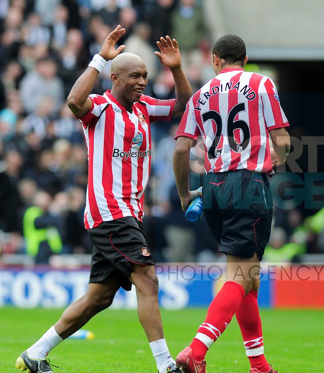 Sunderland's El Hadji Diouf celebrates at the final whistle with Anton Ferdinand.