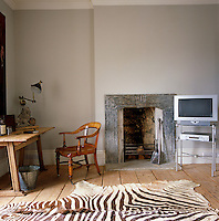 The modern television contrasts with the antique wooden desk and chair in the living room