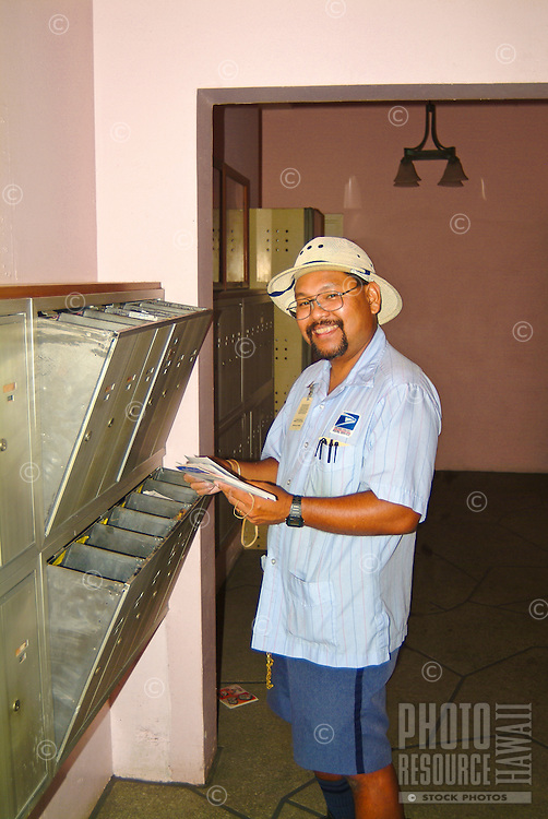 Filipino mail carrier delivering mail to an condominium building in Honolulu. Filipinos arrived in Hawaii a hundred years ago as immigrants recruited to work on the sugar plantations.