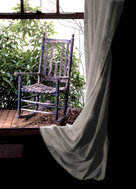 An old rocking chair sits on a front porch of an abandoned house scheduled for demolition.