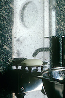 In the bathroom a circular stainless steel wash basin is set against walls of black-and-white marble