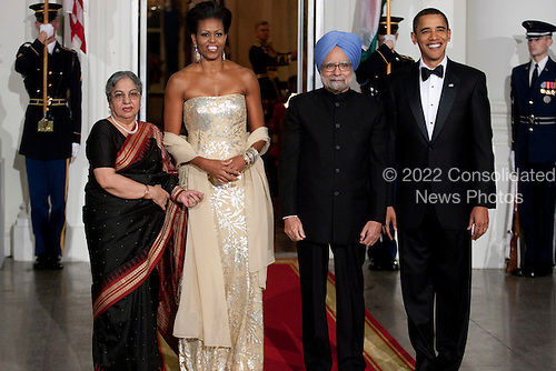 Washington, DC - November 24, 2009 -- United States President Barack Obama, right, and U.S. First Lady Michele Obama, second from left, greet Manmohan Singh, India's prime minister, and his wife Gursharan Kaur upon arrival for the State Dinner at the White House in Washington, D.C., U.S., on Tuesday, November 24, 2009. Obama welcomed India's role as a rising and responsible global power, saying the U.S. will follow through on a civilian nuclear agreement and work to expand trade and investment ties with the world's largest democracy. .Credit: Andrew Harrer - Pool via CNP