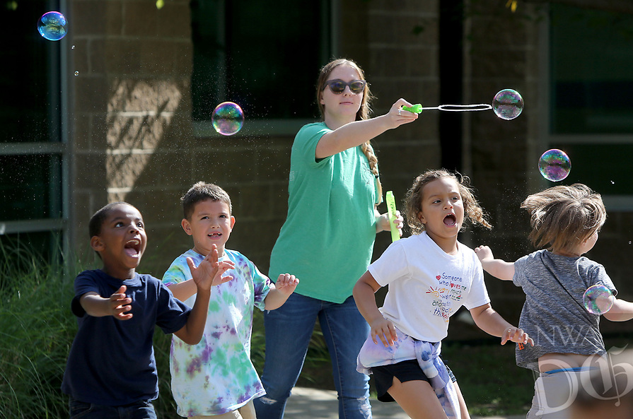 NWA Democrat-Gazette/DAVID GOTTSCHALK  Flaura Pemberton, a kindergarten aid at Owl Creek School, releases bubbles Tuesday, April 18, 2017, as students chase them during  a Soar Celebration at the school in Fayetteville. The school received a top ten ranking in the state from from Niche.com. Niche is a website that gathers comprehensive data about United State schools and neighborhoods. Students flew kites and released bubbles.
