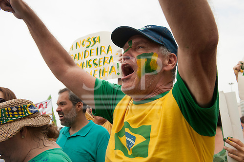 A man with his face painted in the Brazilian national coloiurs chants in protest. Rio de Janeiro, Brazil, 15th March 2015. Popular demonstration against the President, Dilma Rousseff in Copacabana. Photo © Sue Cunningham sue@scphotographic.com.