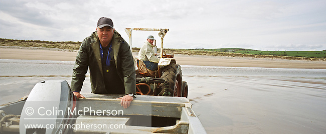 Bob Ritchie pushes his coble (boat) towards his 'jumper' nets used to catch wild Atlantic salmon at Kinnaber, Angus. The once-thriving Scottish salmon netting industry fell into decline in the 1970s and 1980s when the numbers of fish caught reduced due to environmental and economic reasons. By 2007, only a handful of men still caught wild salmon and sea trout using traditional methods, mainly for export to the Continent.