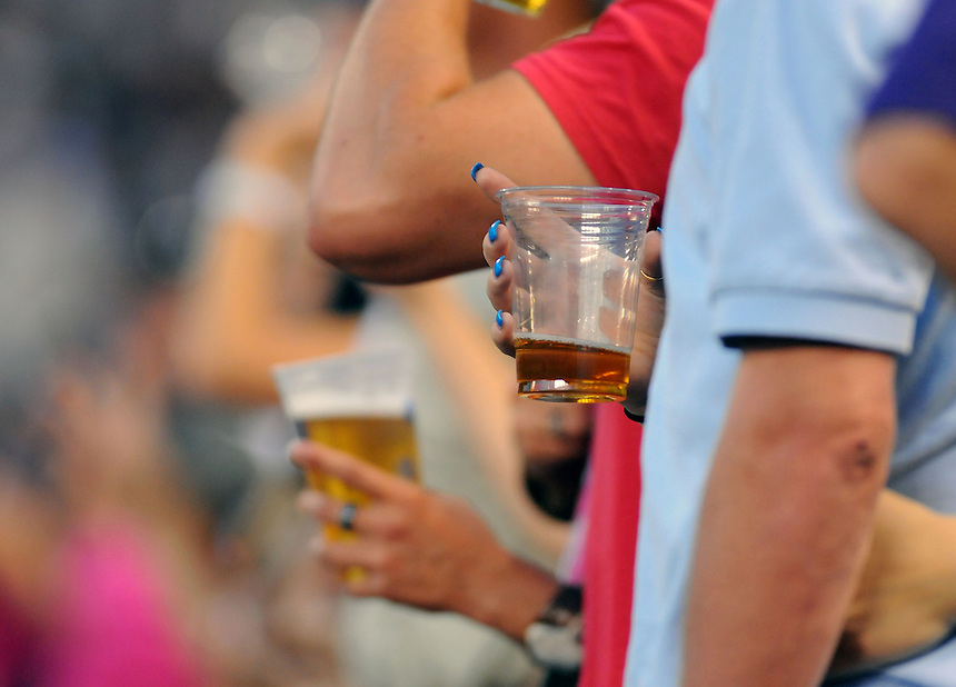 10 JULY 2010: The hands of fans hold nearly empty beers during the 7th inning stretch during a regular season Major League Baseball game between the Colorado Rockies and the San Diego Padres at Coors Field in Denver, Colorado. The Rockies beat the Padres 4-2.  *****For Editorial Use Only*****