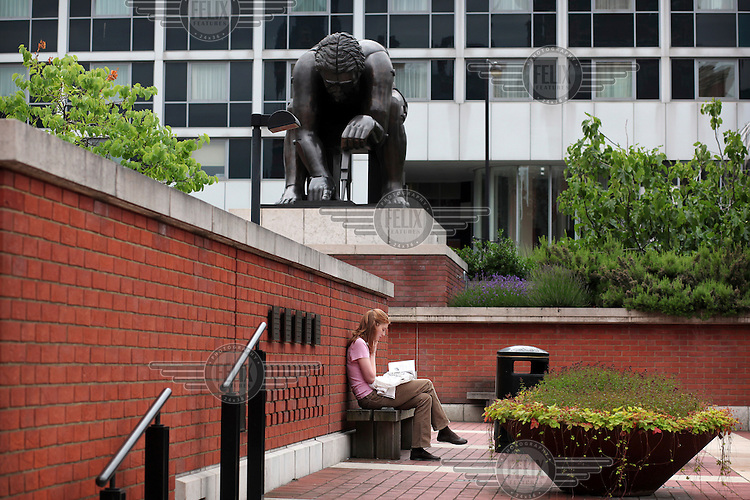A woman reads a book under a statue outside The British Library in London. The statue of Isaac Newton is by the sculptor Eduardo Paolozzi.