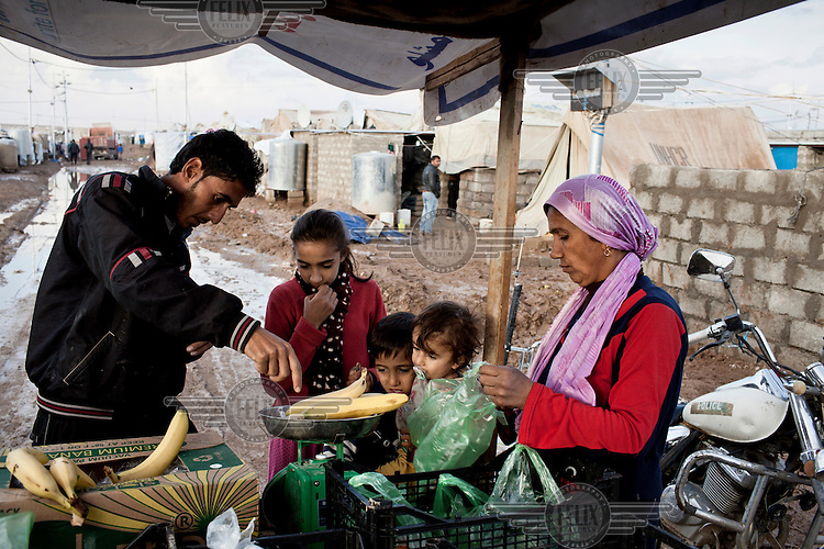 A man sells bananas to Syrian refugees living in Domiz Refugee Camp.