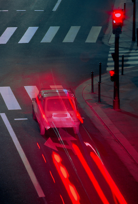 Une voiture freine a un feu rouge. *** A car stops at the traffic light.
