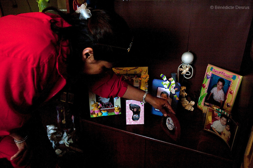 """April 26, 2009 - Mexico City, Mexico - The grandmother of Oscar Corona Perez looks at photos of her dead grandson in her apartment in Mexico City. Oscar, 5 years old, died yesterday after 8 days of treatment at """"La Raza"""" national medical center. The family was told on Friday that the medication and operations that had been done had no effect as Oscar had a new illness with no treatment. The next morning he died at 11:00 AM of pneumonia caused by swine Flu. The death toll has risen to over 80 people in Mexico City, and 929 people have the disease. All dead bodies with the influenza must be cremated. Photo credit: Benedicte Desrus / Sipa Press"""