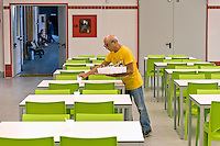 """ROME, ITALY - SEPTEMBER 24: A Voluntary prepares the lunchroom at the hostel  """"Don Luigi Di Liegro"""" of the Caritas of Rome in Via Marsala, Rome. The new facility of 500 for the evening canteen and 300 beds to the hostel,  hosts marginalized people. The hostel opened in 1987 has been renovated to make it more efficient, the social reintegration of the guests  on September 24, 2016 in Rome, Italy."""