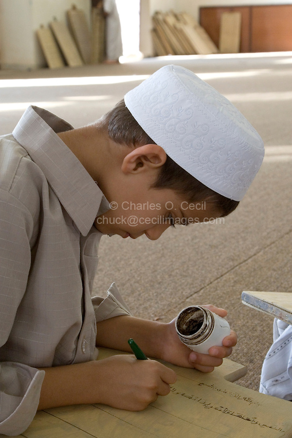 Zliten, Libya. Boy Writes Verses from the Koran on his Prayer Board.  He wears the traditional white hat, the tagiyah.  He studies to memorize the Koran, working under the supervision of a teacher, or muqri.