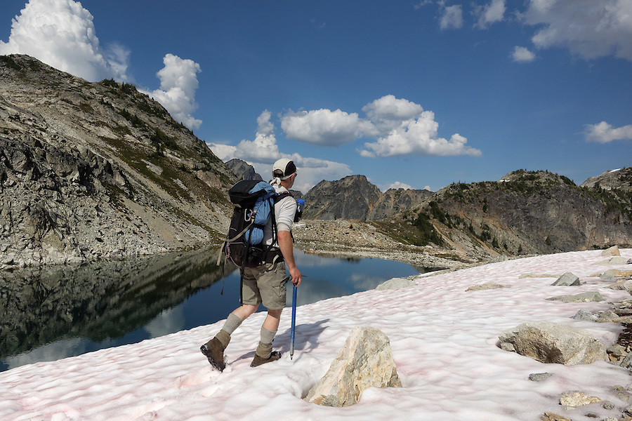 Man hiking on snow field above Silent Lakes, North Cascades National Park, Skagit County, Washington, USA