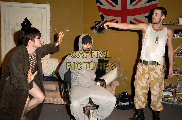 "JAMES ALEXANDROU, RAY PANTHAKI  & KEVIN WATT.The ""In My Name"" photocall, Old Red Lion Theatre, London, England..March 25th, 2008.full length acting stage play brown housecoat bathrobe glasses grey gray top hoodie hoody hands sitting beard facial hair bound gagged white vest top  camouflage trousers gun pistol shooting .CAP/CAN.©Can Nguyen/Capital Pictures."