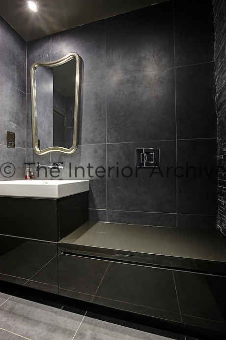 A modern grey tiled bathroom  A mirror hangs on the wall above a washbasin set on a unit. A toilet is concealed in a unit with a lid.