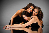 Portrait of three Hispanic women leaning on each other