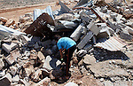 A Palestinian boy inspects the remains of their family's makeshift home, which was destroyed by the Israeli army in the West Bank village of Aqaba in the northern Jordan Valley, Thursday, July 3,2014. Palestinian security sources said the Israeli army destroyed at least eight makeshift homes which the army said were illegally built in the area. Photo by Shadi Hatem