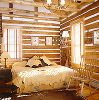 A rustic bedroom in the restored interior of an original log cabin with a bed covered in hide