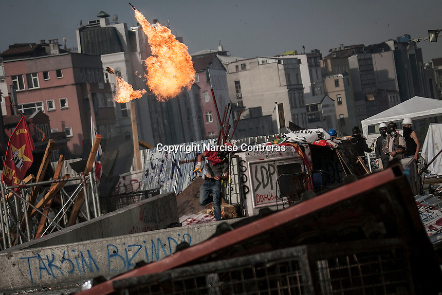 In this Tusday, Jun. 11, 2013 photo, a protester throws a coctail molotov to the anti-riot police duriing clashes at the streets of Taksim Square in Istanbul,Turkey. (Photo/Narciso Contreras).